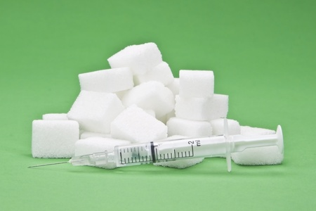 sugar cubes with an syringe as a symbol for diabetes Stock fotó
