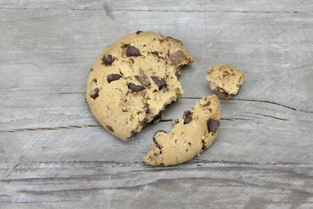 Close-up of a broken chocolate chip cookie on old wood