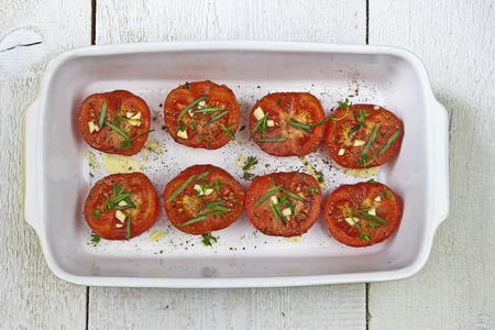baked tomatoes in a white casserole Stock Photo