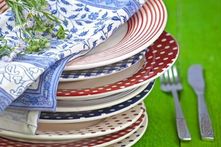 rustic and colorful plates on a green wooden table