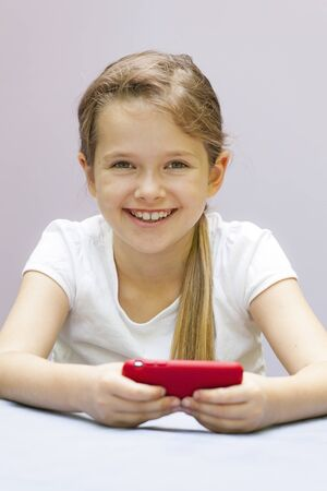 seven year old: a seven year old girl who plays with a mobile phone