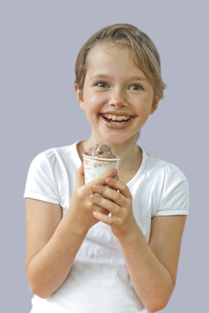 seven year old girl who is eating a chocolate ice cream photo