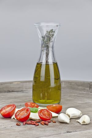 halved tomatoes with slices of mozzarella and flavored olive oil, garlic and peppers