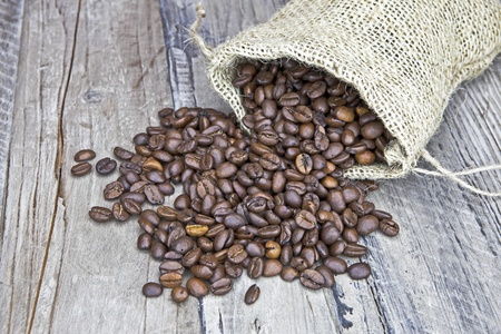 Coffee beans in a jute bag on a wooden table