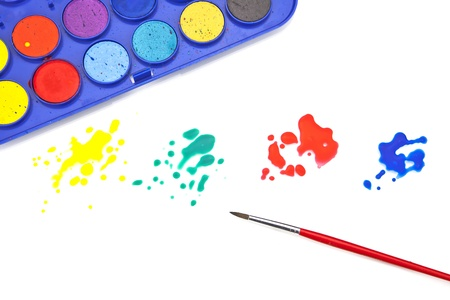 Splashes of color and a paint box with water colors and a brush