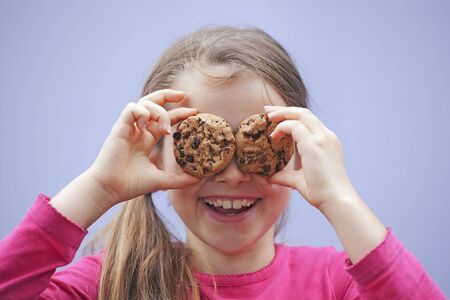 a seven-year-old girl eating chocolate cookies photo
