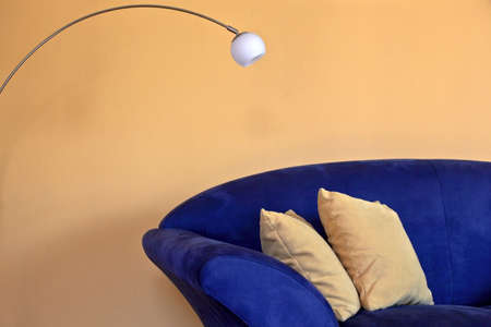 a blue sofa with reading lamp and yellow pillows and walls
