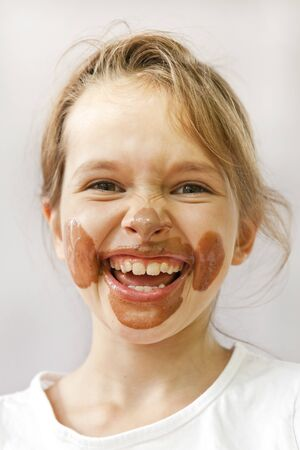 a seven-year-old with chocolate ice cream in the face that looks forward Stock Photo - 9876227
