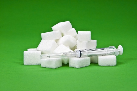 sugar cubes with a syringe as a symbol for diabetes Stock Photo