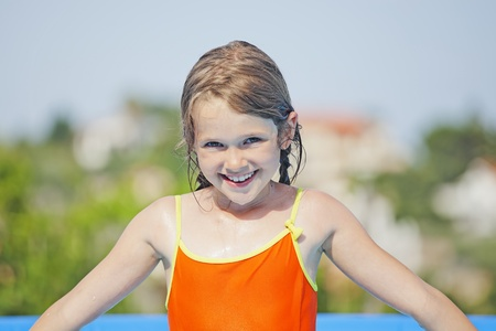 seven-year old girl playing in summer in the pool Stock Photo