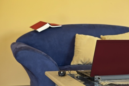 a laptop to work on a blue couch with a book photo