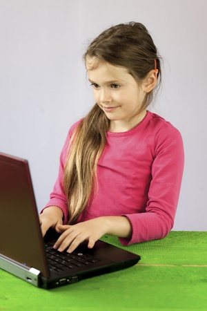 a seven-year-old girl on a laptop to make homework Stock Photo - 10032370