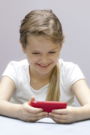 a seven year old girl who plays with a mobile phone photo