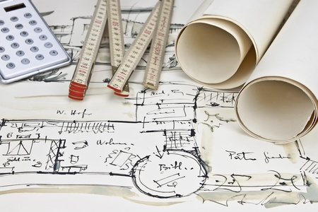 the blueprint of a house with two paper rolls, a calculator and a rule