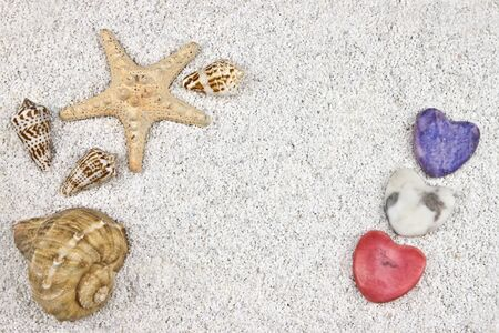 a seastar and several shells in white sand with three hearts Stock Photo - 10097977