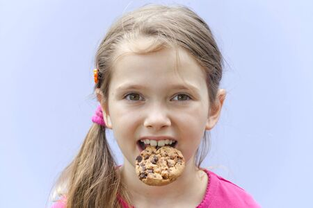 a seven-year-old girl eating chocolate cookies Stock Photo - 10097949