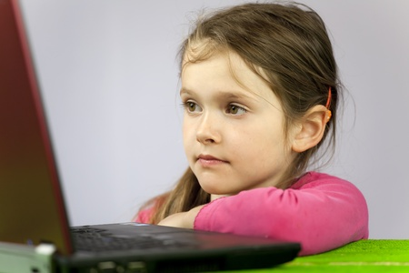 a seven-year-old girl on a laptop to make homework Stock Photo - 10097952