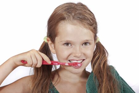 likeable: eight year old girl with a toothbrush and a towel to clean the teeth