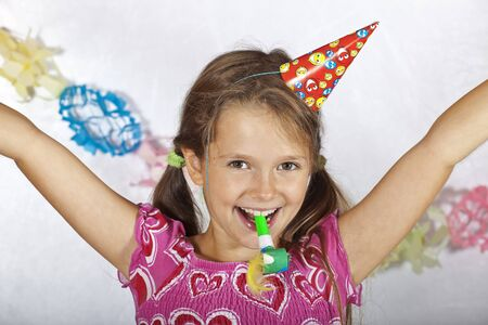 eight year old girl with party hat and trumpet on a childrens festival