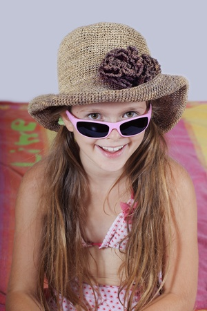 eight year old girl with hat, sunglasses and beach towel Stock Photo