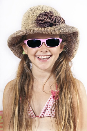 eight year old girl with hat, sunglasses and beach towel photo