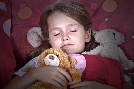 an eight-year-old girl in bed with blanket and pillows and stuffed animals Stock Photo