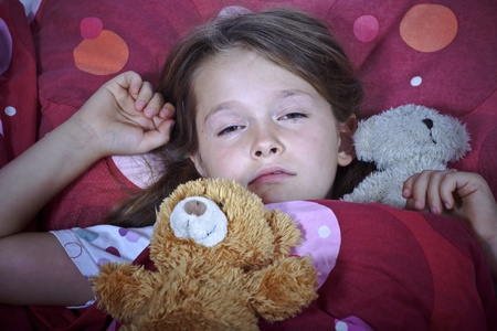an eight-year-old girl in bed with blanket and pillows and stuffed animals Stock fotó