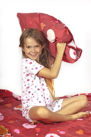 eight year old girl in bed doing a pillow fight photo