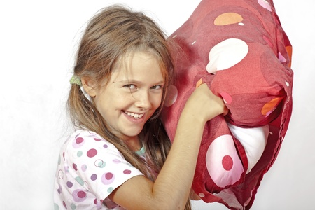 throw cushion: eight year old girl in bed doing a pillow fight Stock Photo