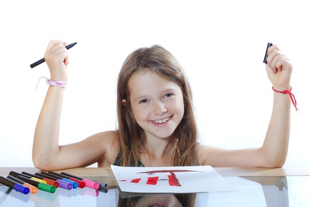 eight year old girl draws a picture with markers