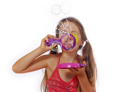 eight year old: eight year old girl playing with soap bubbles