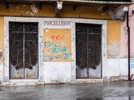 Rotta in ferro battuto di un macellaio abbandonato nel centro della città di Carrara Archivio Fotografico - 79729398