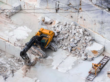 Extraction of marble blocks with the aid of a large mechanical shovel equipped with crawler tracks Archivio Fotografico