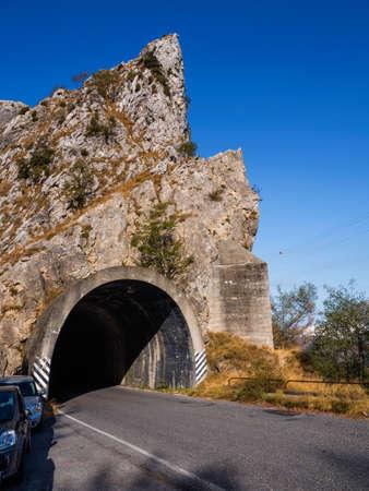 Rock sponge crossed by a gallery along a mountain road Archivio Fotografico
