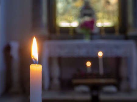 The flame of a candle with the church altar in the background Archivio Fotografico - 104855999