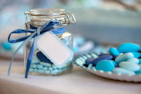party favors: birth in light blue candy container glass and paper plate Stock Photo