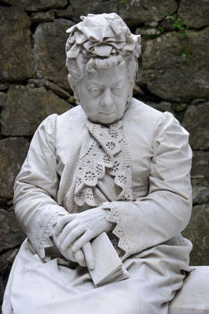 saddened: sculpture of elderly woman saddened by the loss of a relative