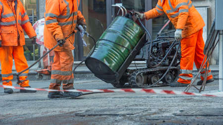 Man s work in road resurfacing in the city Stock Photo