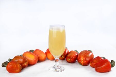 Cashew nuts isolated with glass of fruit juice on white background.