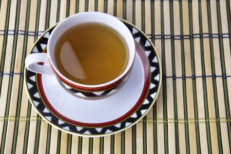 A cup of refreshing green on a wooden mat.