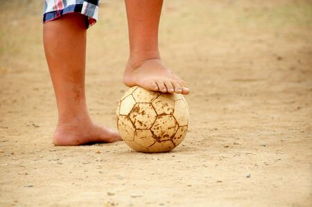 poor child playing barefoot football Zdjęcie Seryjne