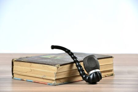 pipe, old book on the table Stock Photo