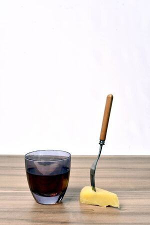 glass of alcoholic drink with cheese on the table on white background.