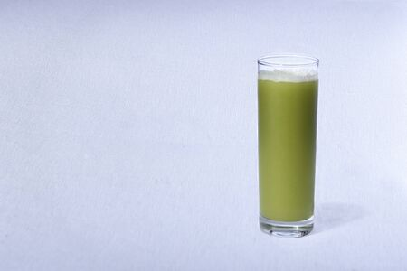 green juice with natural fruits on white background.