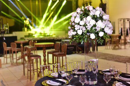 Een luxe boeket verse bloemen in een kristallen vaas op de feesttafel en een elegante portie in het restaurant. Stockfoto