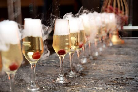 crystal glasses with sparkling cherry and dry ice with blurs and noise
