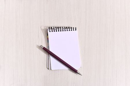 notepad with a pen on the table in aerial view with space for text