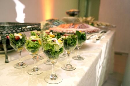 finger food, table with small salads served in crystal bowls on blurred background with noise Zdjęcie Seryjne