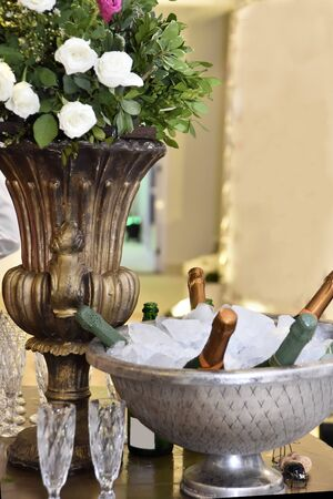table decorated with flower pot, ice bowl with bottles of sparkling champagne on blurred background