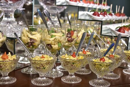 small portions of food pasta, salad, olive oil, spices in glass cups with blurs in the photo
